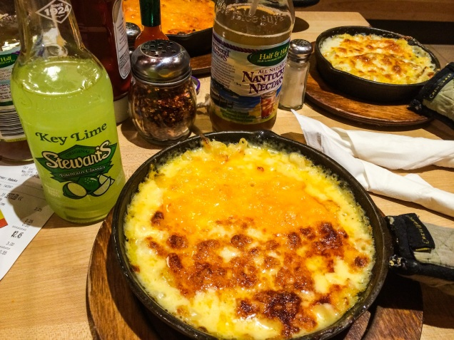 Two small pans of macaroni and cheese with a bottle of Half & Half and a bottle of Key Lime soda