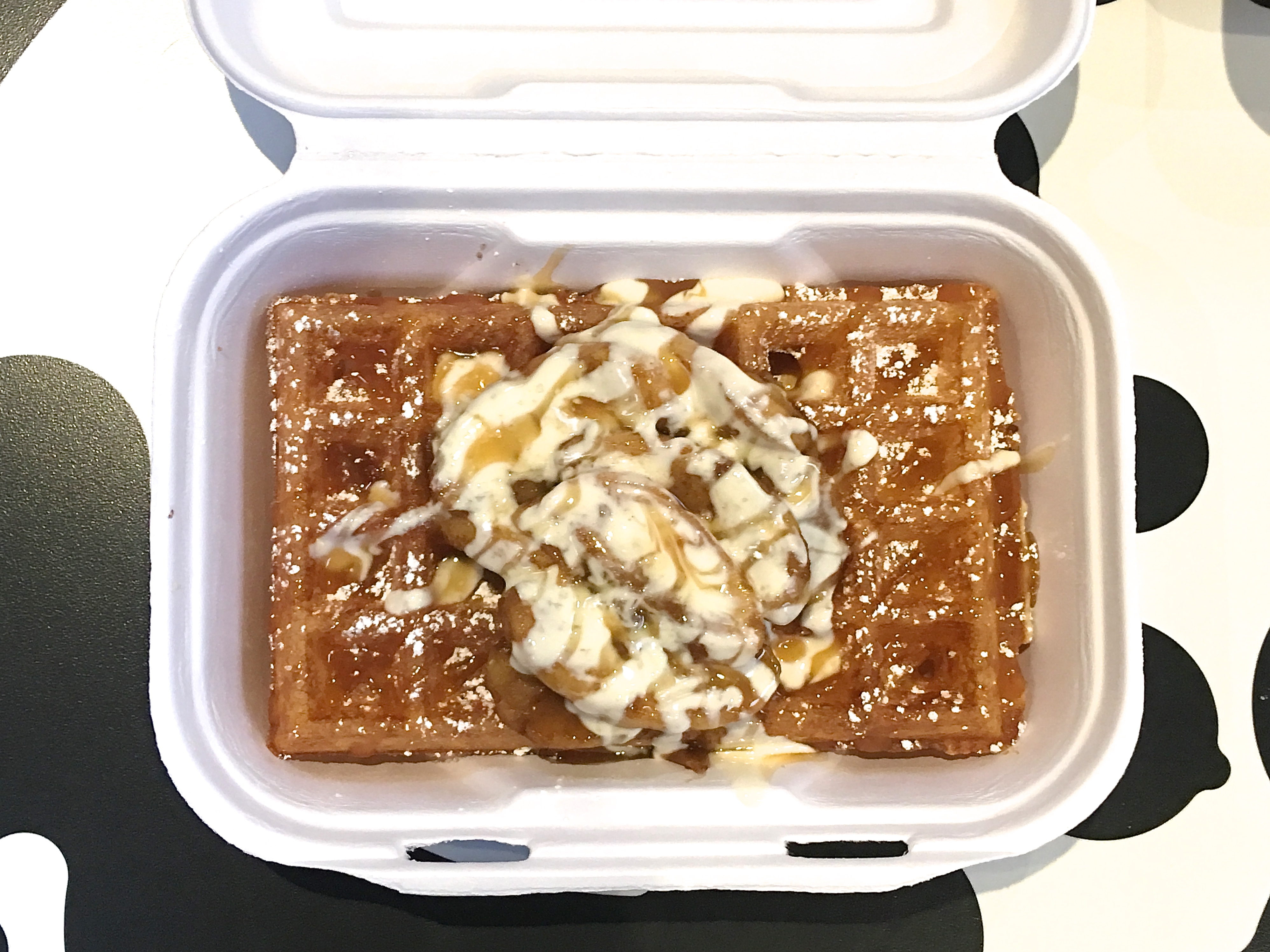 A waffle with cinnamon apples, whipped cream, and caramel drizzle on top