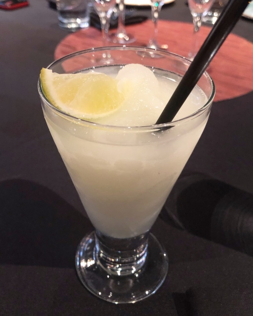 A frozen margarita garnished with lemon