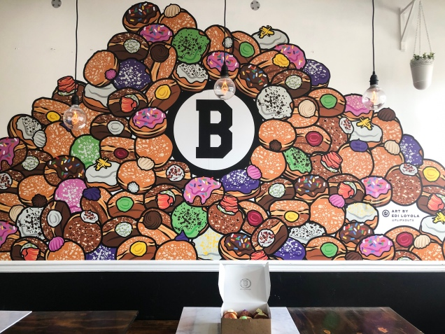 B. Doughnut's doughnut mural with a dozen of their doughnuts on the table. | Apple of My Eye