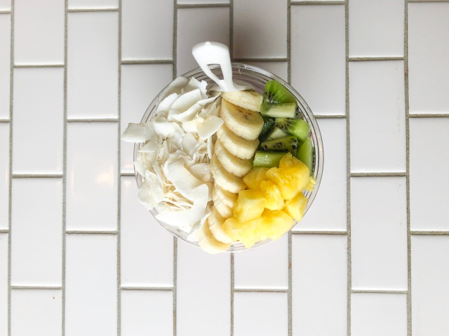 An overhead view of Rutabaga Juicery's smoothie bowl, which is made with pitaya, mango, banana, coconut oil, agave, and coconut water and is topped with granola, coconut, banana, kiwi, and pineapple.