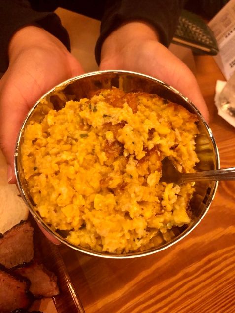 A bowl of corn pudding being held by two hands.