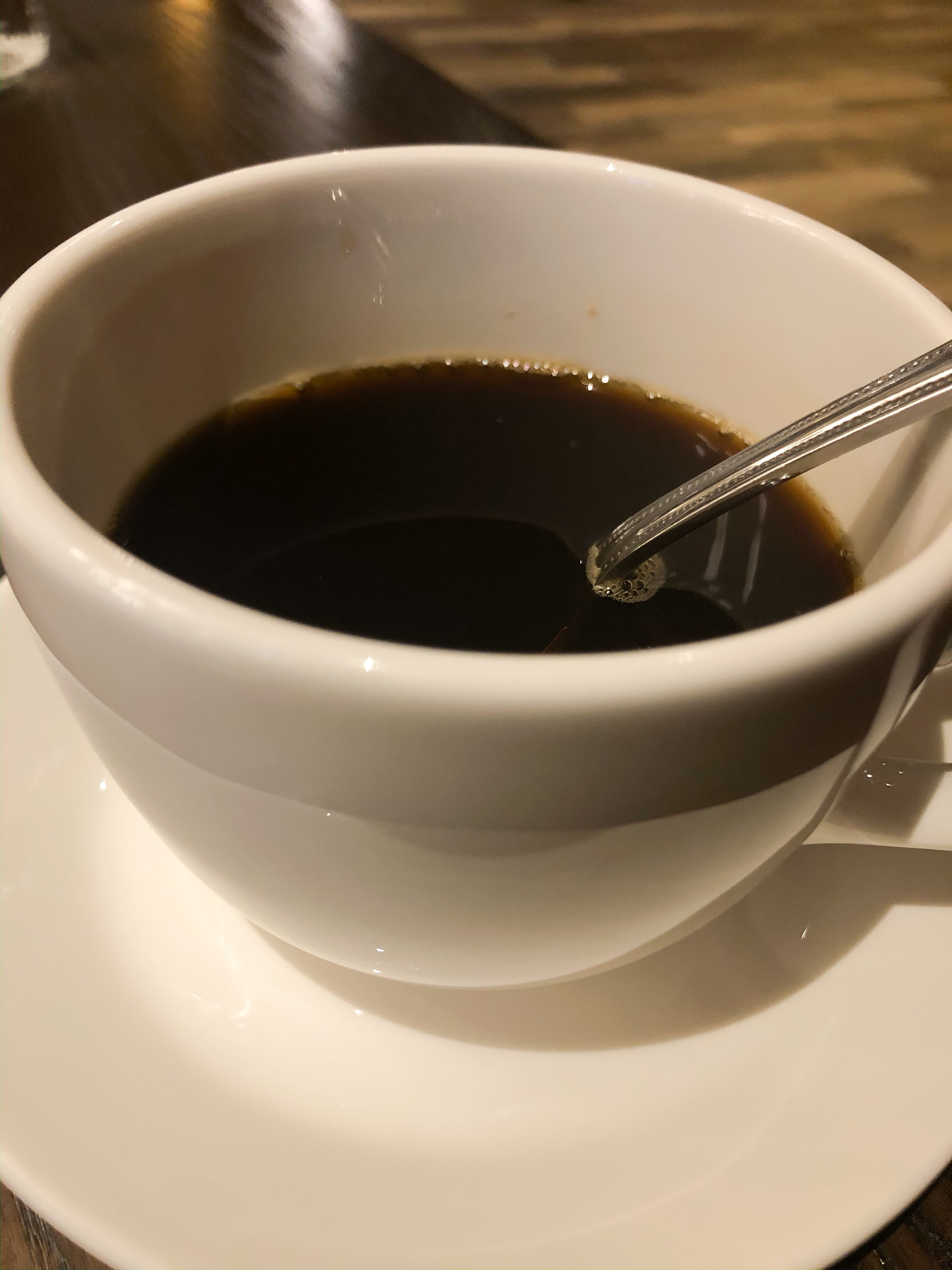 A cup of coffee with a spoon in it.