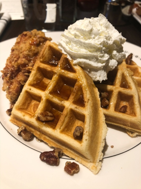 Waffles topped wtih pecans, syrup and whipped cream with a side of fried chicken.