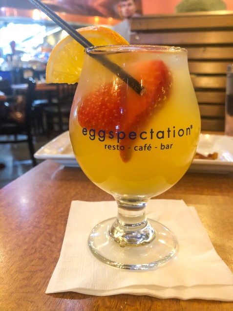 An orange alcoholic beverage with strawberries and an orange slice.