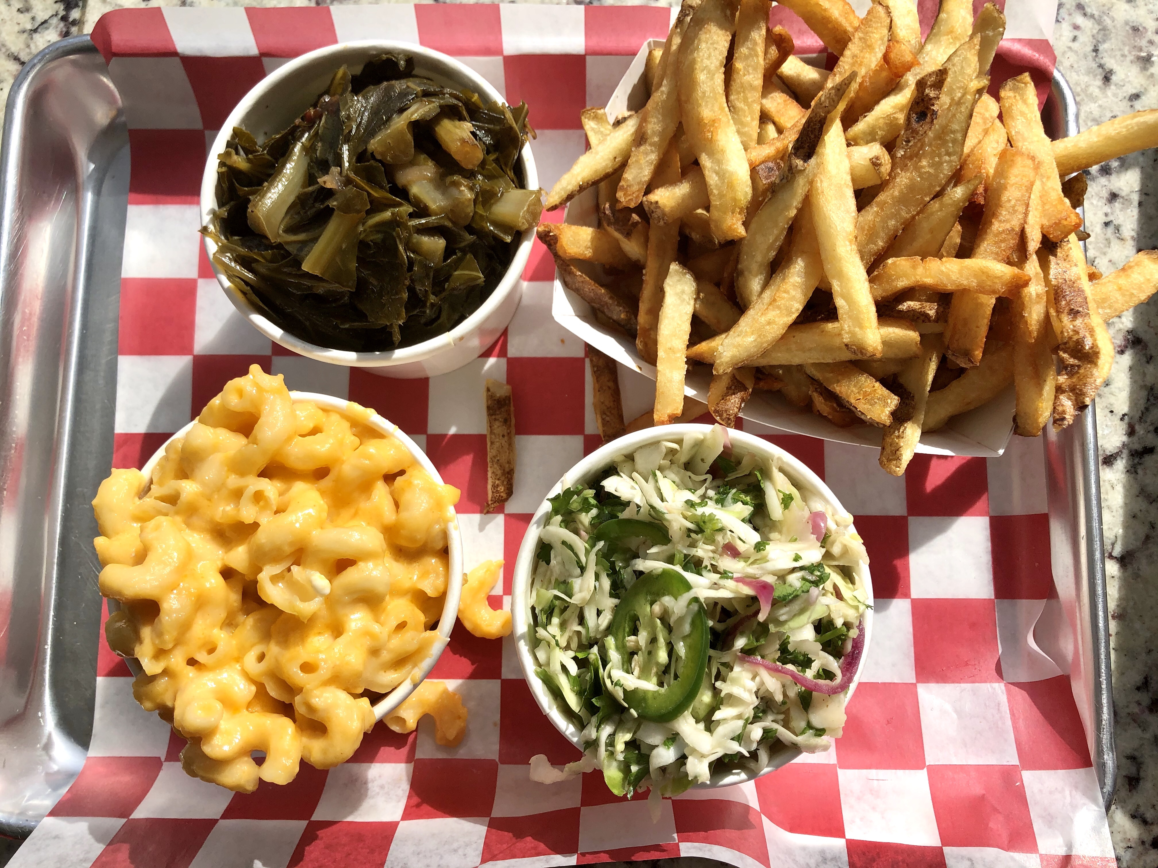 Dish sides in different cups: collard greens, fries, macaroni and cheese, and coleslaw